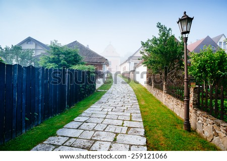 Cobblestone road in small old Europe town. Grassy roadside. Wooden fence. Blue sky. Poprad, Slovakia. - stock photo