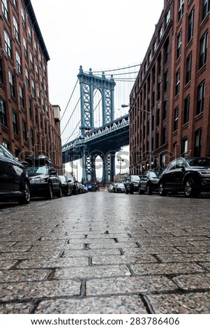 Cobblestone street alley in Brooklyn with Manhattan Bridge in background after rain - stock photo