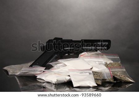 Cocaine and marihuana in packages and handgun on grey background - stock photo