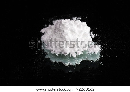 Cocaine drugs heap on a black mirror, close up view