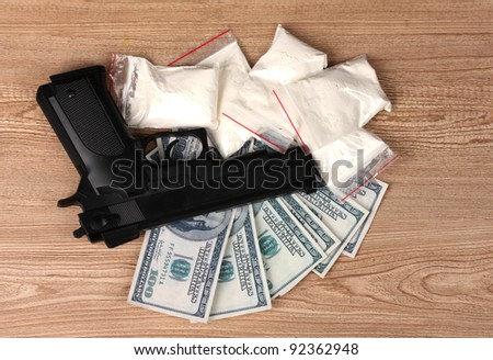 Cocaine in packages, dollars and handgun on wooden background - stock photo
