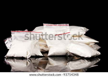 Cocaine in packages on black background - stock photo