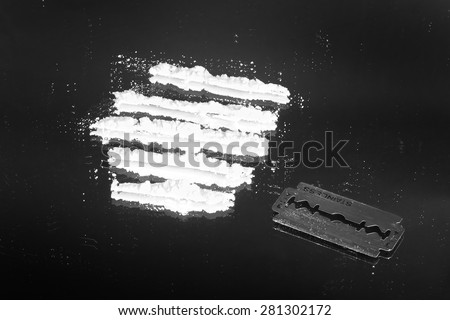 Cocaine powder in lines and razor blade on a grunge black background  - stock photo