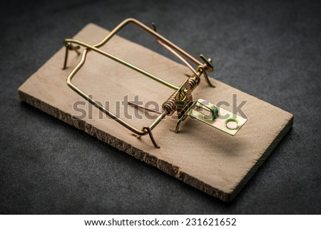 Cocked empty mousetrap on dark background. Selective focus.   - stock photo