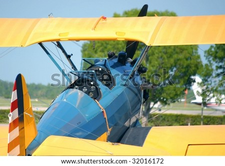 cockpit of a vintage bi-wing aircraft parked at an airport. The view is from behind the aircraft. The fuselage is blue, the wings and the tail are bright yellow, the rudder is red and white stripes. - stock photo