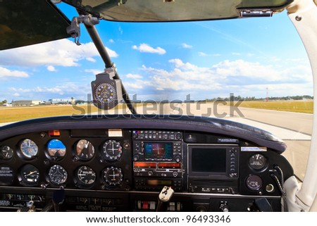 Cockpit view from small aircraft taking off from runway - stock photo