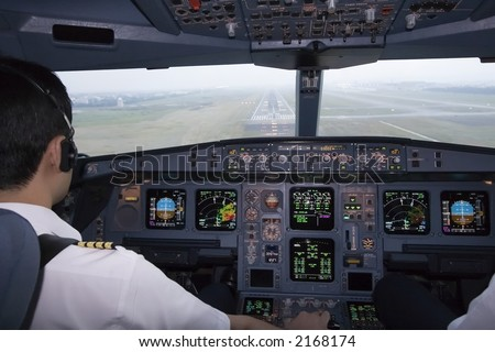Cockpit view of an airline pilot about to land on final approach - stock photo