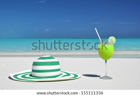 Cocktail and hat on the beach of Great Exuma, Bahamas - stock photo