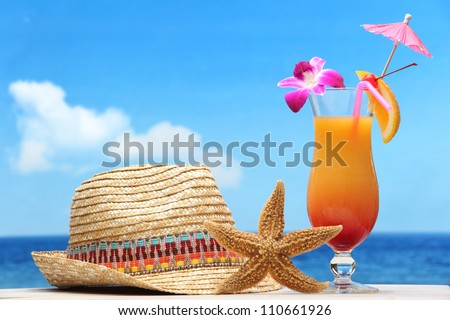 Cocktail and straw hat on beach - stock photo