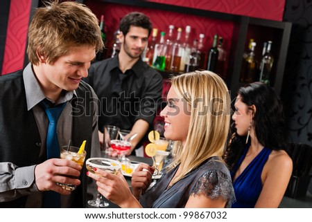 Cocktail bar young happy couple friends enjoy drinks - stock photo