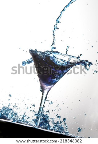 Cocktail being poured into martini glass - stock photo