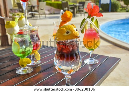 cocktail drinks on the side of a swimming pool in tropical summer holiday resort