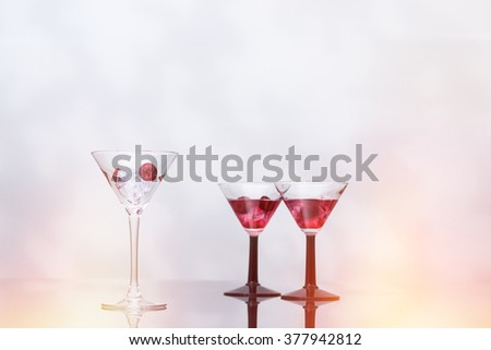 Cocktail glass filled with ice and cherries with two cocktails in the background