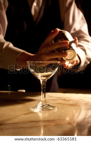 cocktail glass in front of barkeeper - stock photo