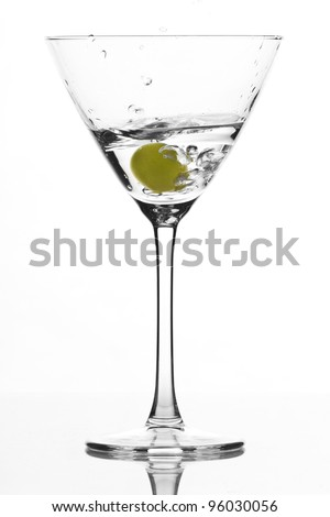 cocktail glass isolated on white ground with green falling olive