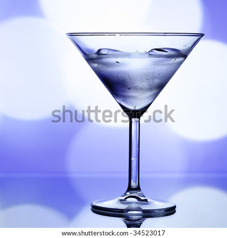Cocktail glass with ice and holiday lights in the background - stock photo