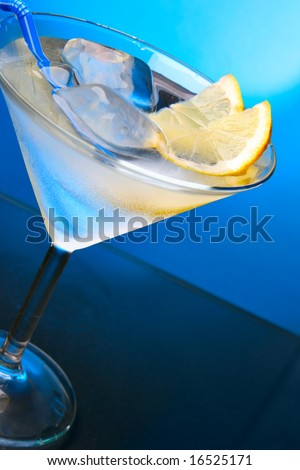 Cocktail glass with ice cubes and lemon slice close-up - stock photo