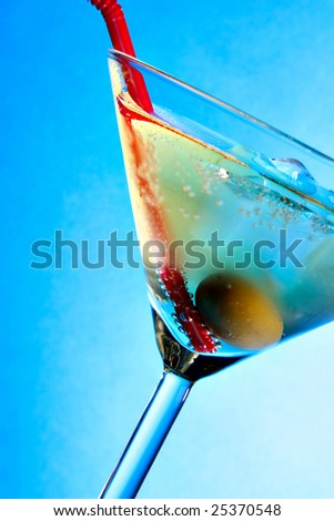 Cocktail glass with olive and red straw over blue background - stock photo