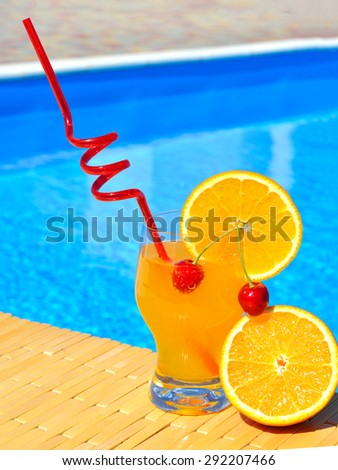 Cocktail glass with orange and cherry on pool background - stock photo