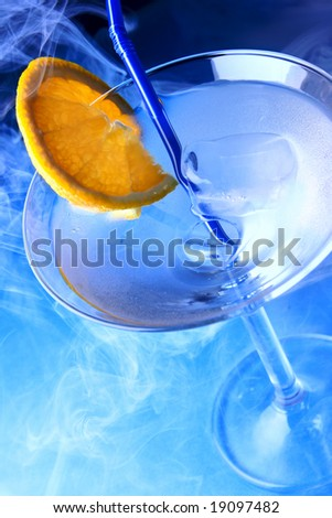 Cocktail glass with orange slice and blue smoke in the background - stock photo