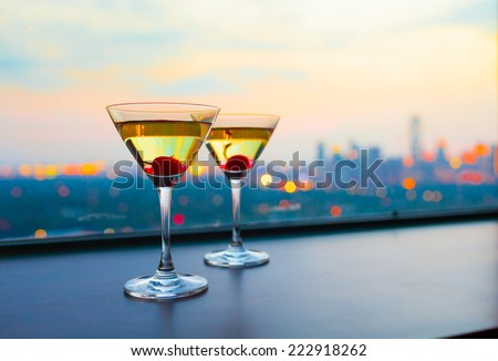 Cocktail glasses against city view - stock photo