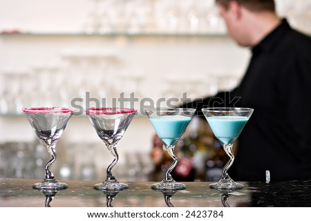 Cocktail glasses on bar, with bartender - stock photo