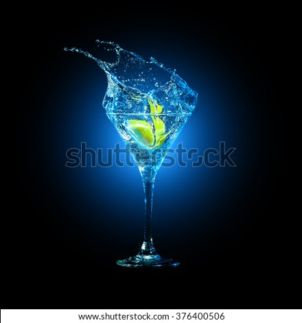 cocktail in glass with splashes and lemon on dark background. Party club entertainment. Mixed light - stock photo