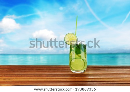 cocktail into glass and cubes of ice on the beach  - stock photo