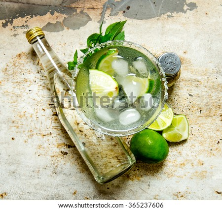 Cocktail Margarita . Ingredients cocktail - limes, ice , tequila, salt and liqueur on the old background .  Top view - stock photo