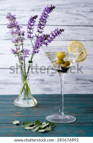 Cocktail martini with ice and olives on a wooden background. - stock photo