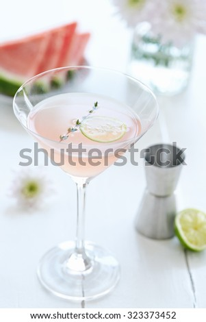 Cocktail mocktail drink in a martini glass decorated with a slice of lime and garnish with a slice of watermelon and flowers in the background - stock photo
