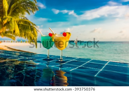 Cocktail near the swimming pool on the background of the Indian Ocean, Maldives. - stock photo