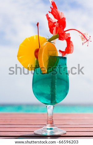 Cocktail on a beach table with a tropical fruit - stock photo