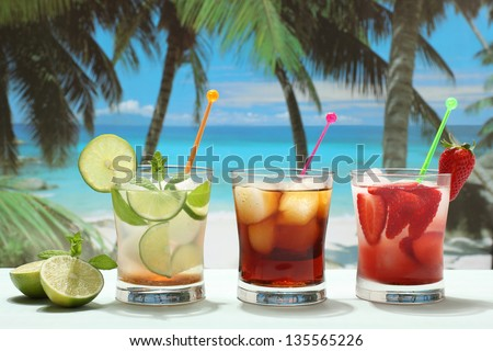 cocktail rum and coke mojito with lime strawberry and cola on the beach - stock photo