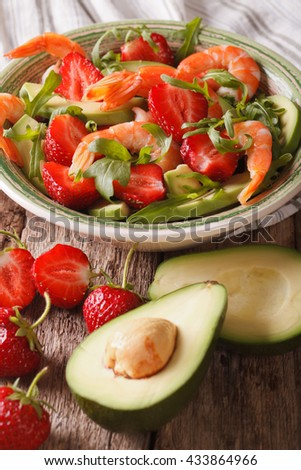 Cocktail salad with strawberries, avocado, shrimp and arugula close-up on a plate. Vertical - stock photo