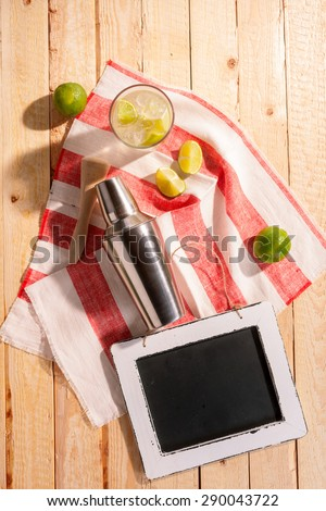 Cocktail shaker and an iced tropical cocktail with lime and lemon on a striped bar cloth on a wooden table, overhead view with a blank slate for your beverage recipe - stock photo