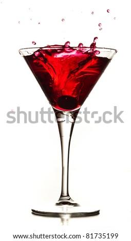 cocktail splashing into glass on white background - stock photo