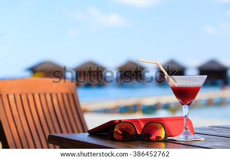 cocktail, touch pad and glasses on beach resort - stock photo