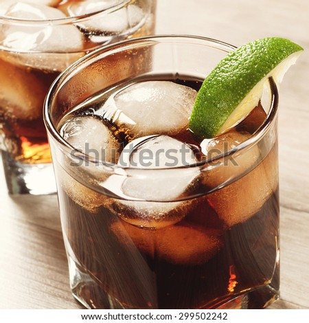 Cocktail with cola and ice on wooden table. in a glass with a cocktail, put a slice of lime  - stock photo