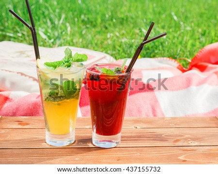 Cocktail with ice and lemon slice on wooden table - stock photo