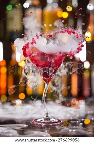 Cocktail with ice vapor and splashing liquid on bar desk, close-up. - stock photo