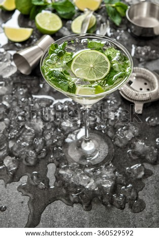 Cocktail with lime, mint and ice. Bar drink accessories on black desk - stock photo