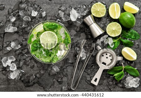 Cocktail with lime, mint and ice. Bar drink accessories on black table background. Alcoholic and nonalcoholic cold drinks. Selective focus - stock photo