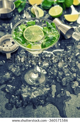 Cocktail with lime, mint and ice. Bar drink accessories. Vintage style toned picture - stock photo