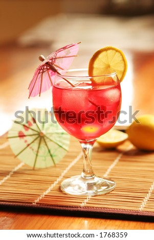 Cocktail with mini umbrella and lemon slice