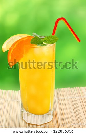 Cocktail with tangerine and lemon juice with ice cubes on a blurred background. - stock photo