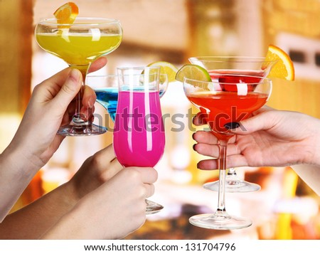 Cocktails in hands in cafe