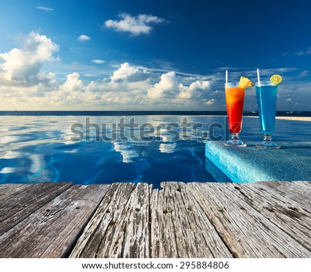 Cocktails near the swimming pool and old wooden pier - stock photo