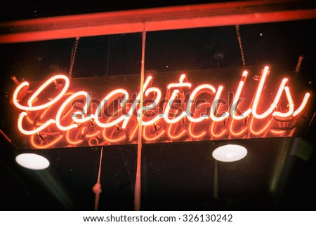 Cocktails Neon Sign Vintage. Cocktails sign in neon hanging in a bar window. Edited with subtle vintage effects. - stock photo