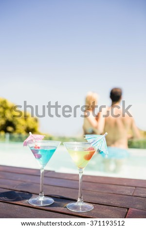 Cocktails on pools edge and couple in the pool - stock photo